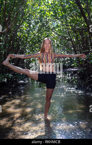Young woman practicing yoga (Extended Hand-to-Big-Toe Pose - Utthita Hasta Padangustasana) in a natural setting - Fort Lauderdale, Florida, USA - Stock Photo
