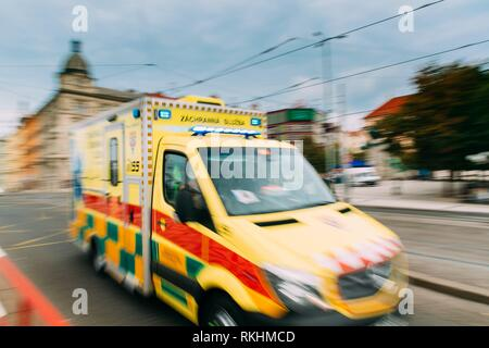 Prague, Czech Republic. Moving With Siren Bright Yellow Emergency Ambulance Reanimation Van Car On Street. Ambulance Car In Blurred Motion Background. - Stock Photo