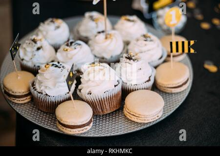 Dessert Sweet Tasty Cupcakes And Macarons In Candy Bar On Table. Delicious Sweet Buffet. Wedding Decorations. - Stock Photo