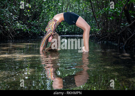 young woman upward bow or wheel pose yoga pose