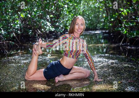 Young woman practicing yoga (One-Legged King Pigeon - Eka Pada Rajakapotasana) in a natural setting - Fort Lauderdale, Florida, USA - Stock Photo