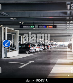 BASEL, SWITZERLAND - MAR 22, 2018: Perspective view to interior of modern airport parking with row of cars - Stock Photo