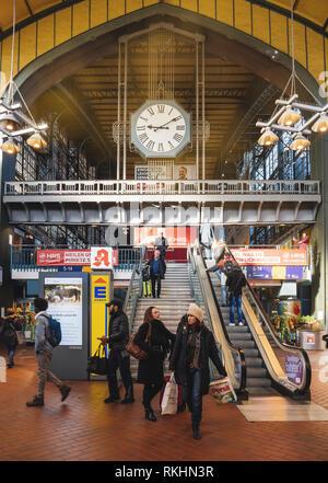 HAMBURG, GERMANY - MAR 20, 2018: Commuters on escalator under big clock inside Hamburg central train station - Stock Photo