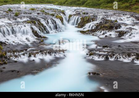 Detail of bright powerful Bruarfoss waterfall in Iceland with cyan water. - Stock Photo
