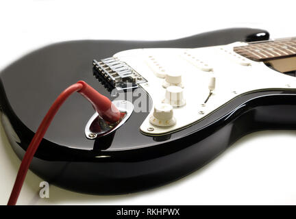 Part of modern electric six string guitar black color with glossy finish with red cord in socket, pickups and control knobs isolated on white backgrou - Stock Photo