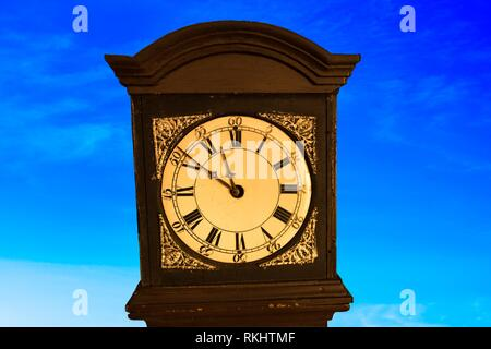 Old grandfather clock in front of sky. - Stock Photo