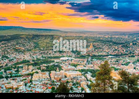 Tbilisi, Georgia. The Scenic Aerial Panoramic Cityscape With Beautiful Dramatic Yellow Sunset, Sunrise On Blue Cloudy Summer Sky. - Stock Photo
