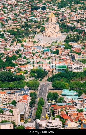 Tbilisi, Georgia. Aerial View Of Baratashvili Bridge Over Kura River And Sameba Complex, Holy Trinity Cathedral, Surrounded By Private Residential - Stock Photo