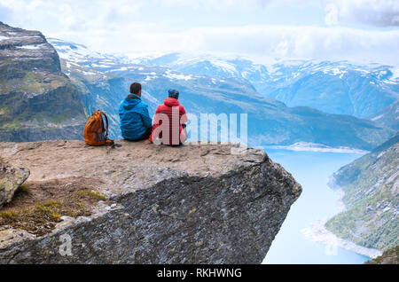 Couple sitting top view on the way to Trolltunga. Location: Scandinavian Mountains, Norway, Stavanger. Concept of freedom and success - Stock Photo