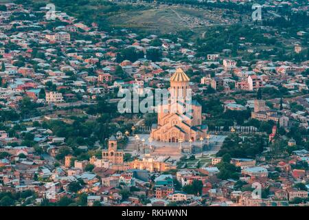Tbilisi, Georgia. Evening Aerial Panoramic View Of Sameba Complex, Holy Trinity Cathedral Surrounded By Populous Residential Area In Summer Dusk. - Stock Photo