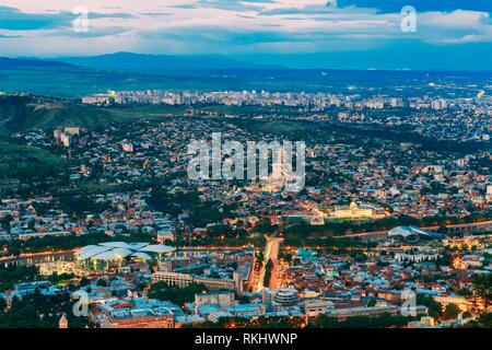 Tbilisi, Georgia. Evening Scenic Aerial Cityscape With All Famous Landmarks In Bright Illumination In Summer Twilight, Blue Cloudy Sky Under Dark - Stock Photo