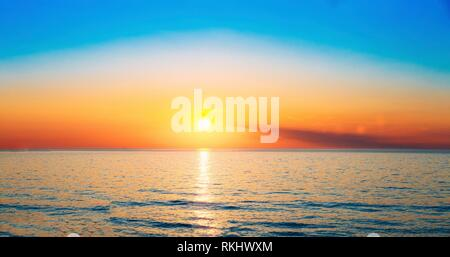 Batumi, Georgia. Sun Is Setting On Horizon At Sunset Sunrise Over Sea Or Ocean. Tranquil Sea Ocean Waves. Natural Sky Blue And Orange Colors. - Stock Photo
