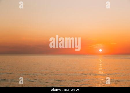 Batumi, Georgia. Sun Is Rising On Horizon At Sunset Or Sunrise Over Evening Sea Or Morning Ocean. Tranquil Waves. Natural Sky Warm Colors. - Stock Photo