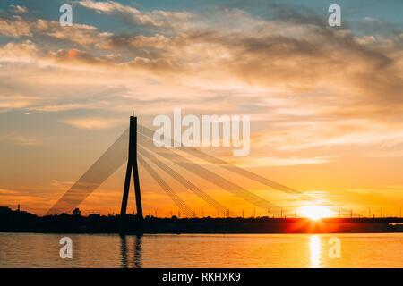 Riga, Latvia. Scenic View Of Vansu Cable-Stayed Bridge Over The Daugava River, Western Dvina In Bright Sunset Or Sunrise Time. - Stock Photo