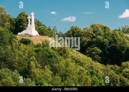 Vilnius, Lithuania. Famous White Monument Three Crosses On The Bleak Hill, Overgrown With Lush Green Vegetation In Summer, Blue Sky. - Stock Photo