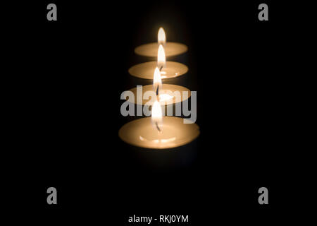 Close up shot of several lined up tea light candles in the dark with focus changing from back to the front. - Stock Photo