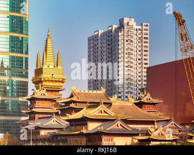 Jing'an Buddhist Temple in Shanghai, China, surrounded by modern high-rise buildings. - Stock Photo