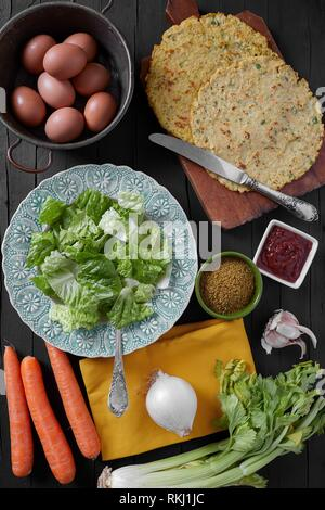 Vegan crepes with eggs, carrots, celery, onions, garlic and spices. Top view shot on black wooden background. - Stock Photo