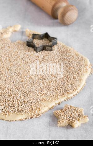 Cutting star shaped biscuits from dough sprinkled with sesame seeds on kitchen paper. - Stock Photo