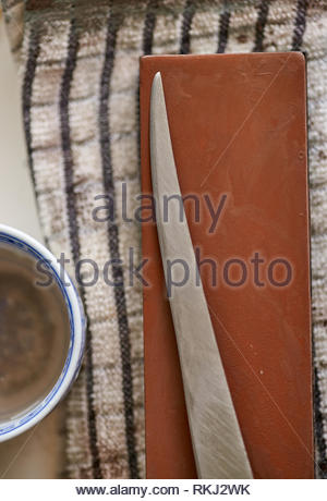 A stainless steel filleting knife lays on a brown sharpening whetstone, which in turn sits upon a black and white cloth; a bowl of dirty water beside. - Stock Photo