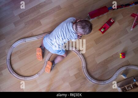 Child boy playing with wooden toy train. Top view. Educational toys. - Stock Photo