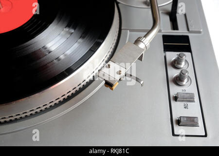 Vintage turntable in silver case with buttons and knobs on control panel with vinyl record with red label isolated on white background. top view close - Stock Photo