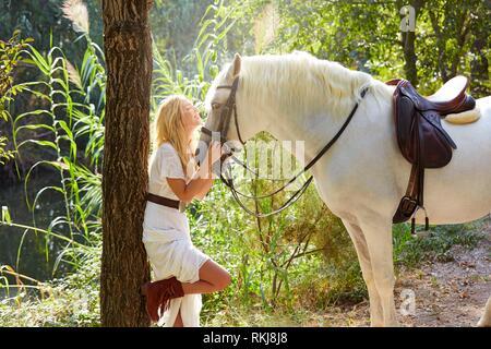 Blond girl hug her white horse in a magic light forest near river. - Stock Photo