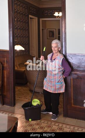 Older woman with mop making the floor of her house. - Stock Photo