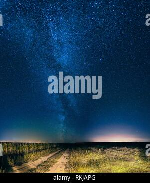 Blue Night Starry Sky Above Country Road In Countryside And Green Field. Yellow City Lights On Background. Night View Of Natural Glowing Stars. - Stock Photo