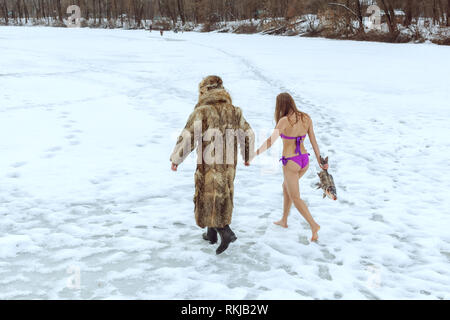 Man in a fur coat and a girl in a bathing suit go hand in hand on the frozen lake. - Stock Photo