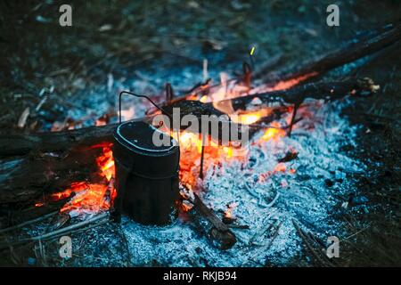 Food Is Cooked Over A Fire In An Old Vintage Retro Marching Pot Dixie. German Wehrmacht Infantry Soldier's Military Equipment Of World War II. - Stock Photo