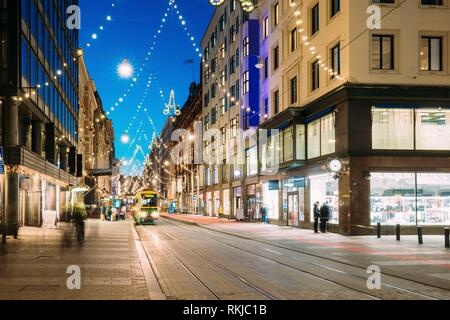 Helsinki, Finland. Tram Departs From Stop On Aleksanterinkatu Street. Street With Railroad In Kluuvi District In Evening Or Night Christmas Xmas New - Stock Photo