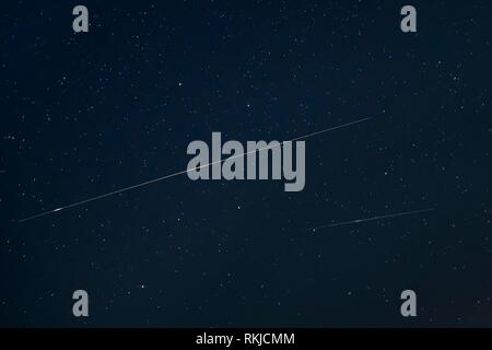 Two Meteoric Tracks In The Blue Night Starry Sky Background. Natural Glowing Stars And Meteorites Trails. - Stock Photo