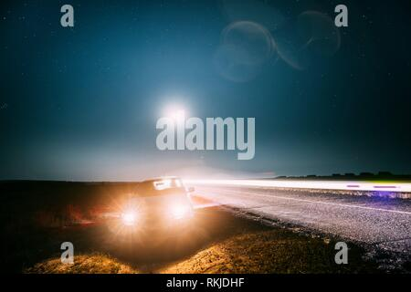 Blue Night Starry Sky Above Country Asphalt Road In Countryside. Sedan Car Parking Near Asphalt Road In Summer Night. Yellow Car Lights And Night - Stock Photo