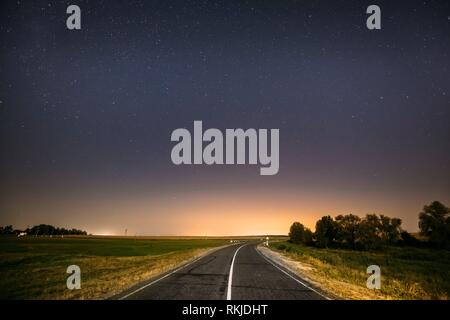 Blue Night Starry Sky Above Country Asphalt Road In Countryside And Green Field. Yellow City Lights On Background. Night View Of Natural Glowing - Stock Photo