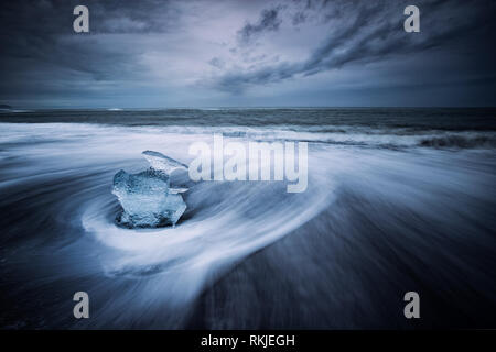 Sea Drifts in around the Icebergs and the Glacial ice that gets swept up on the beach on the black sands at Jokulsarlon, Iceland - Stock Photo