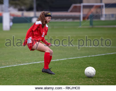 Athletic high school girl competing in a soccer game - Stock Photo