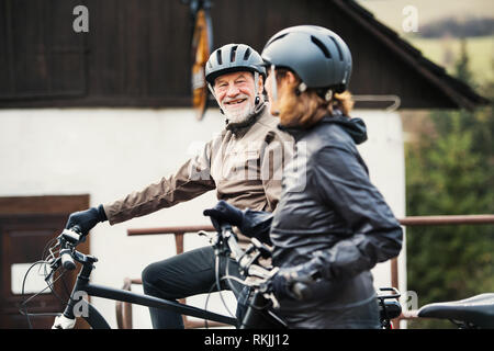 Active senior couple with electrobikes standing outdoors in front of a house. - Stock Photo