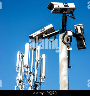 Mobile Phone Mast and CCTV Cameras Against a Blue Sky - Stock Photo