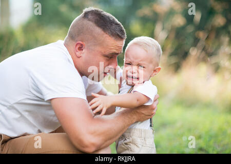 Young father with a small crying toddler son in sunny summer nature. Stock Photo