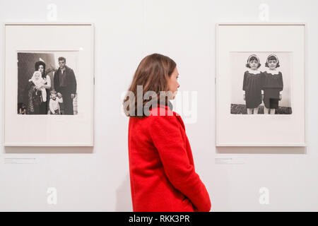Hayward Gallery, London, UK , 12th Feb 2019. A gallery assistant looks at 'Identical twins', Roselle, N.J. 1967, one of Arbus' most well known images. 'diane arbus: in the beginning' includes nearly 100 photographs that redefine the achievement of one of the most prominent and influential artists of the 20th century. Credit: Imageplotter News and Sports/Alamy Live News - Stock Photo