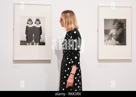 Hayward Gallery, London, UK , 12th Feb 2019. A gallery assistant looks at 'Identical twins', Roselle, N.J. 1967, one of Arbus' most well known images, with 'Mexican Dwarf in his Hotel Room', N.Y.C 1970, also in view (right) . 'diane arbus: in the beginning' includes nearly 100 photographs that redefine the achievement of one of the most prominent and influential artists of the 20th century. Credit: Imageplotter News and Sports/Alamy Live News - Stock Photo