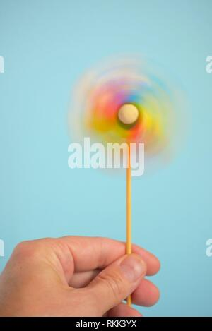 Toy Multi-colored windmill and hand. - Stock Photo