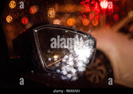 Cinematic rear-view mirror point of view pov personal perspective on modern new electric luxury car driving in the city with defocused bokeh lights on a stormy rainy snow bad weather  - Stock Photo