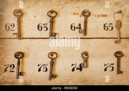 Vintage keys with numbers hanging in an old closet. - Stock Photo
