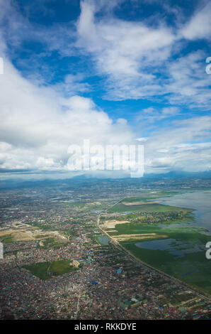 Aerial View of Densely packed communities & neighborhoods near Manila Bay, taken from above by an airplane. - Stock Photo