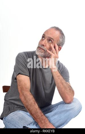 portrait of middle aged man sitting on white. - Stock Photo