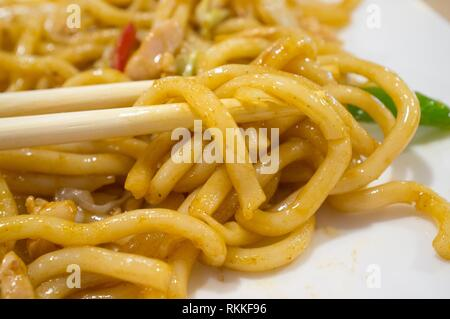 Udon between chopsticks. Type of thick noodle used in Japanese cuisine. - Stock Photo