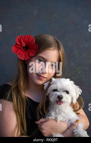 Blond kid girl with maltichon puppy pet dog and hibiscus red flower on hair. - Stock Photo