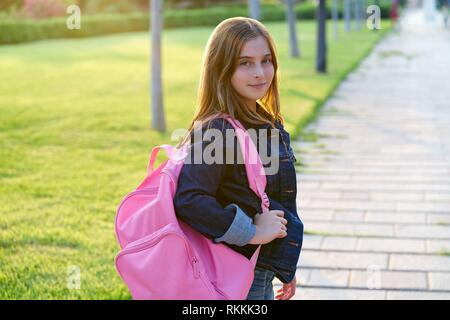 Blond kid student girl with backpack in the park. - Stock Photo